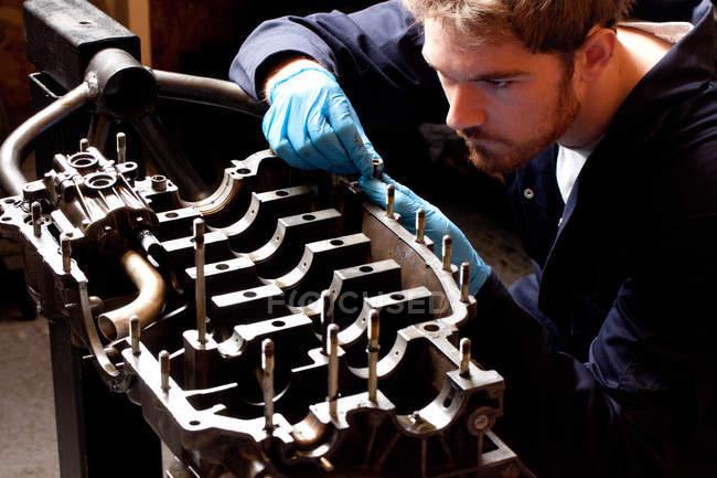 Mécanicien masculin analysant le moteur de voiture — Photo de stock