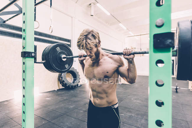 Young male cross trainer weightlifting barbell in gym — Stock Photo