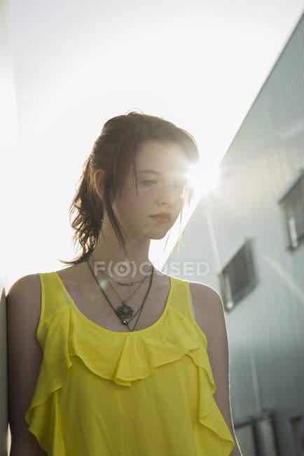 Junges mürrisches Mädchen in gelber Bluse, das nach unten blickt — Stockfoto