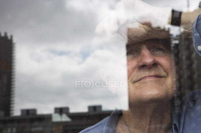 Man smiling and leaning head against window — Stock Photo