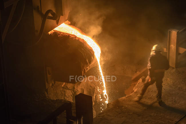Steel worker inspecting pouring molten steel, high angle view — Stock Photo