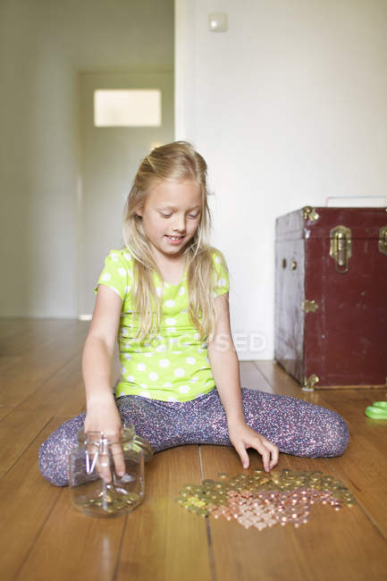 Chica contando monedas de tarro de ahorros - foto de stock