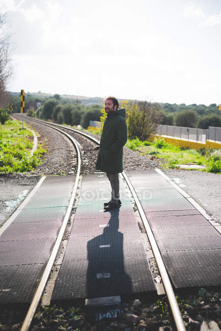 Mid adult man standing on railway crossing — Stock Photo