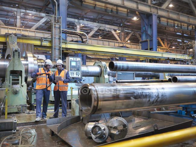 Інженери перевіряють сталеві трубки на інженерному заводі. — стокове фото
