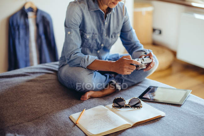Mid adult woman sitting on bed reviewing photographs on digital SLR camera — Stock Photo