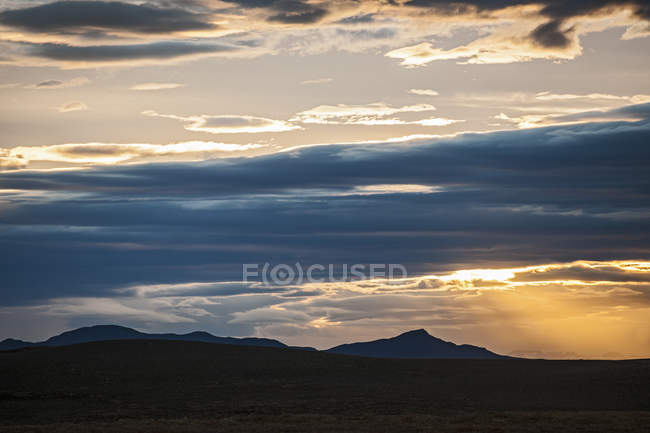 Silhouettes of mountains under cloudy sunset sky — Stock Photo