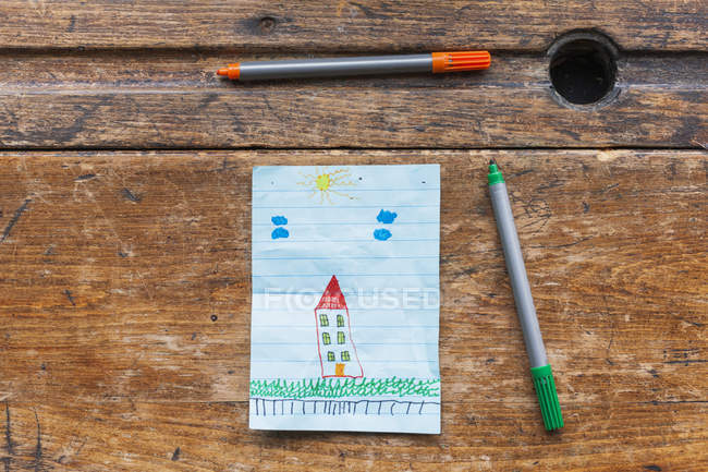 Childs drawing of house with markers on wooden desk — Stock Photo