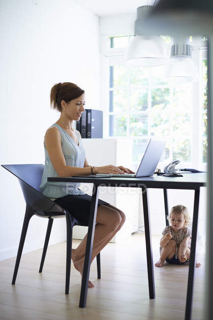 Mid adult mother typing on laptop with toddler daughter under the table — Stock Photo