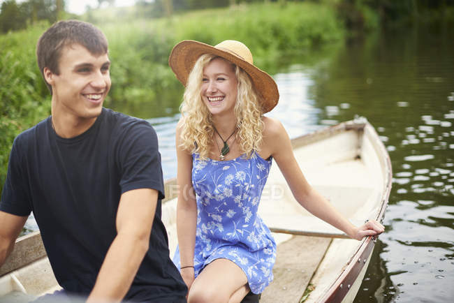 Young couple in rowing boat on rural river — Stock Photo