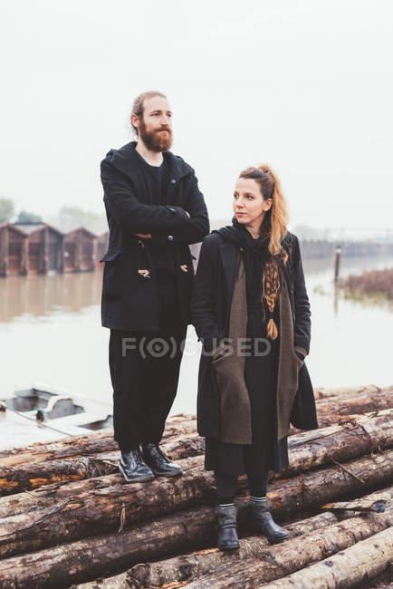 Paar auf Protokolle an nebligen Kanal waterfront — Stockfoto