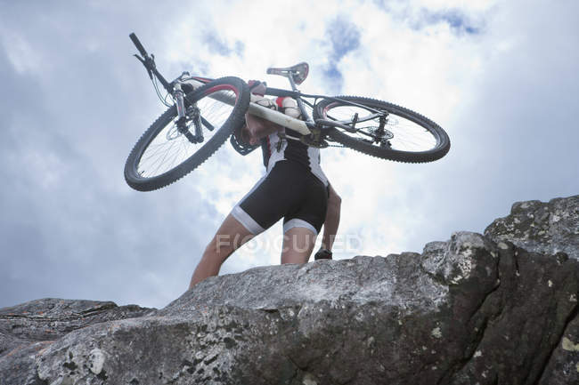 Young man carrying mountain bike on top of rock — Stock Photo