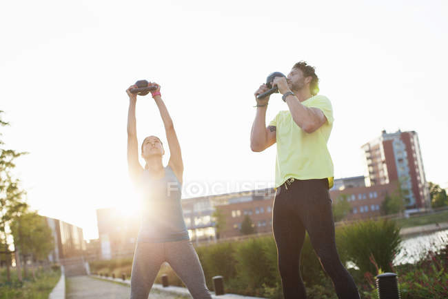 Woman and personal trainer holding up kettlebells at riverside — Stock Photo