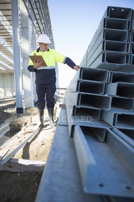 Gerente del sitio revisando las vigas en el sitio de construcción - foto de stock