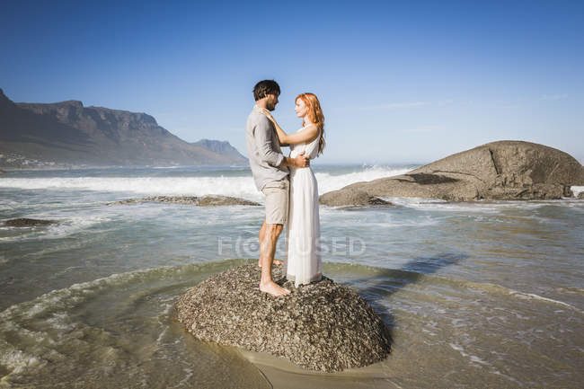 Full length side view of man and woman standing on rock, face to face — Stock Photo
