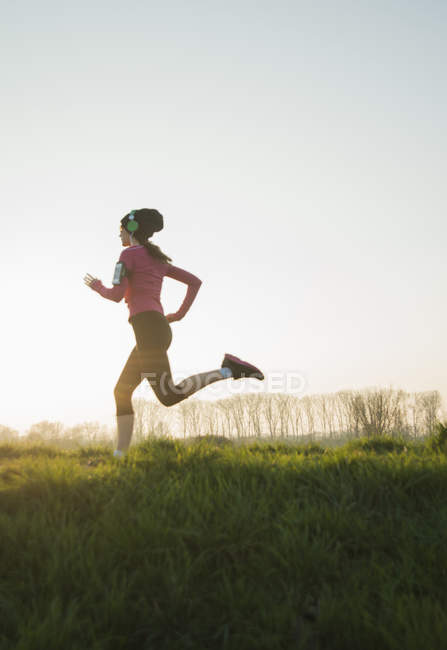 Young female runner listening to headphones whilst running — Stock Photo