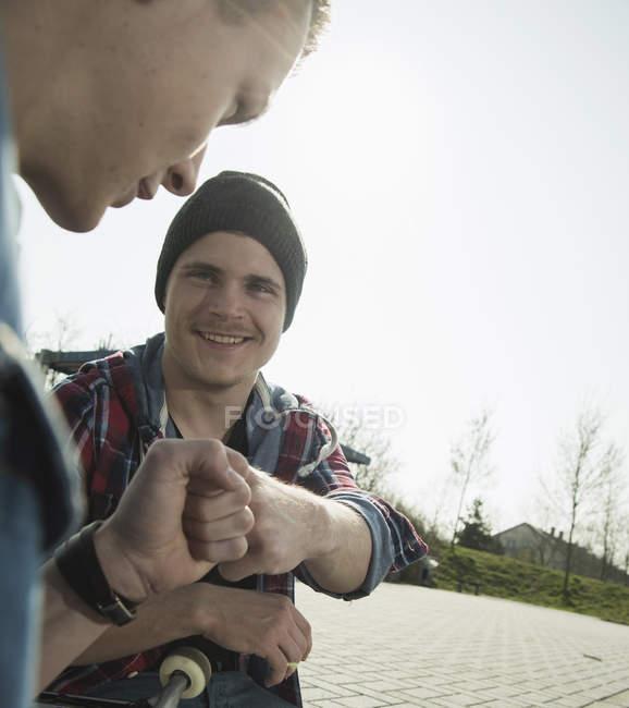 Молоді чоловіки роблять кулаком удар в міських скейтпарк — стокове фото