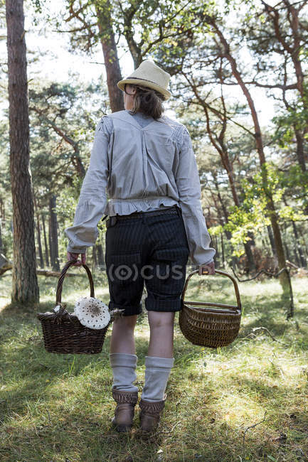 Rear view of female forager carrying baskets of mushrooms in forest — Stock Photo