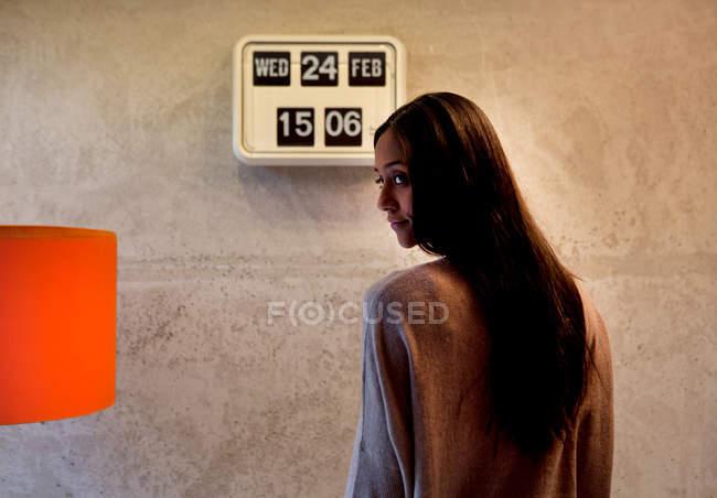 Vista posteriore della donna di fronte a flip orologio distoglie lo sguardo sopra la spalla — Foto stock