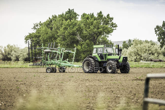 Farmer driving tractor and plough in field — Stock Photo