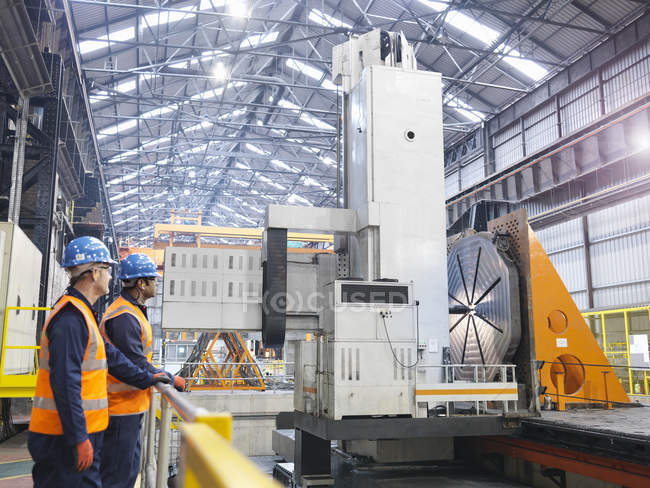 Steelworkers with gantry milling machine in engineering factory — Stock Photo