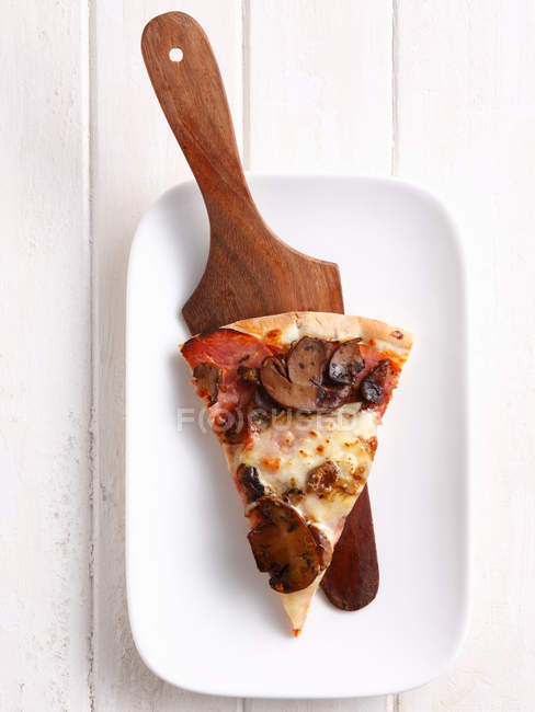 Slice of pizza on platter — Stock Photo