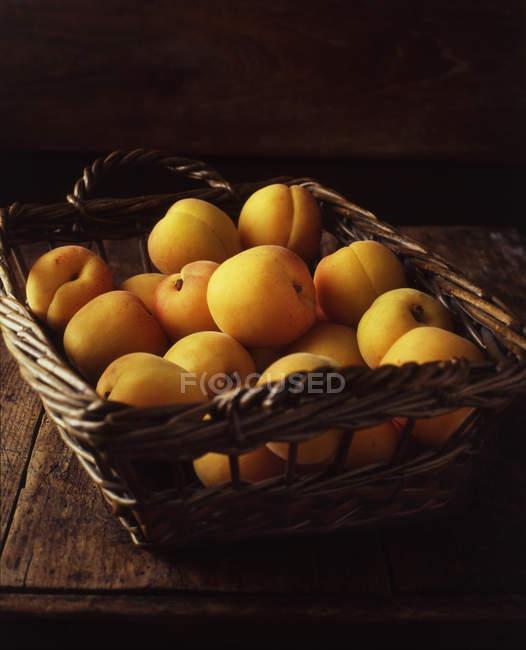 Wicker basket of ripe yellow peaches — Stock Photo