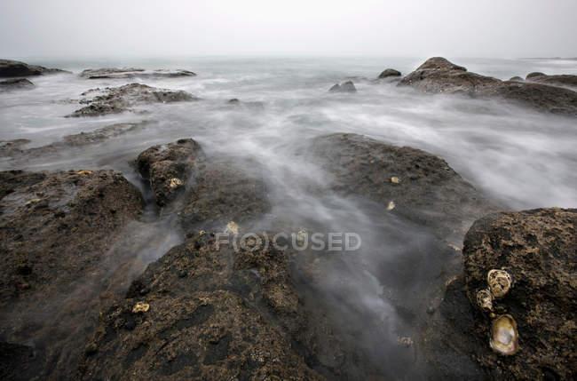 Вода, смывающая камни на пляже — стоковое фото