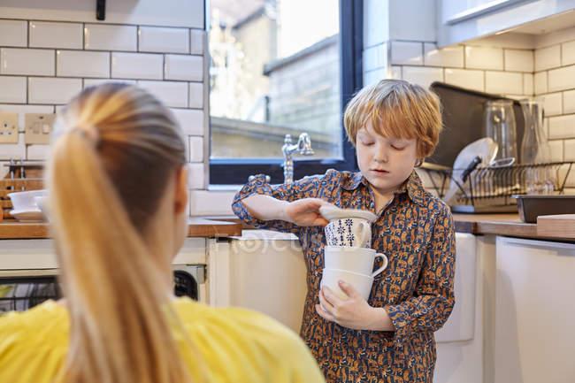 Хлопчик перенесення стек кухлів в кухні — стокове фото
