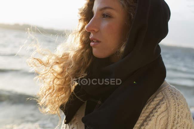 Femme tout enveloppée sur la plage de vent — Photo de stock