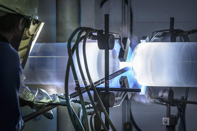 Worker forming large glass tube on lathe in glass factory — Stock Photo
