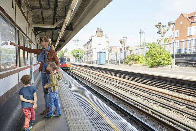 Caucasian mother and son looking at Subway Map on railway platform, London, UK — Stock Photo