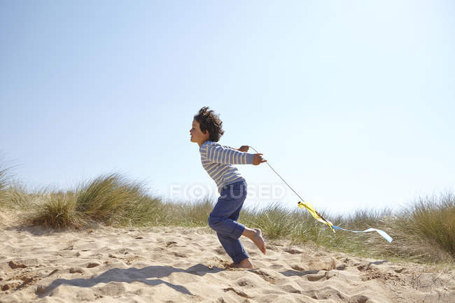 Young boy flying kite on beach — Stock Photo