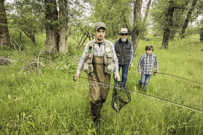 Front view of multi generation family in field carrying fishing rods — Stock Photo