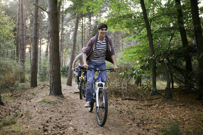 Grupo de jovens amigos do sexo masculino de bicicleta na floresta — Fotografia de Stock