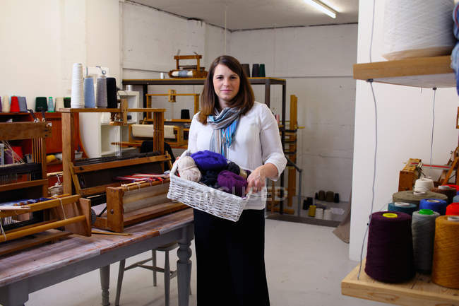 Woman in loom workshop holding container of yarns — Stock Photo