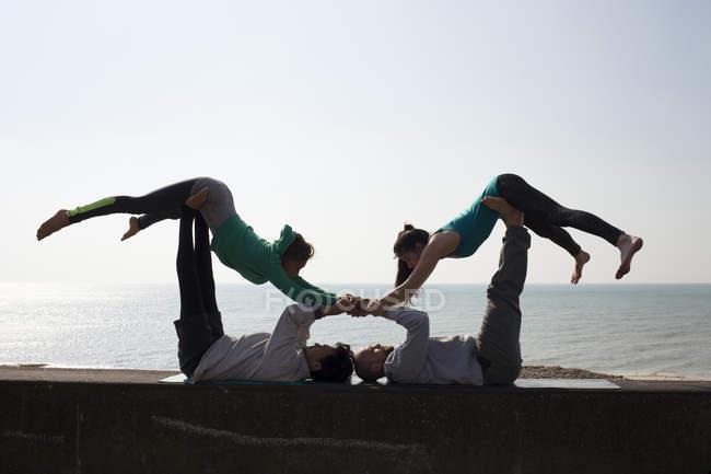 Силуэт мужчин и женщин, практикующих акробатическую йогу на стенах Брайтон Бич — стоковое фото