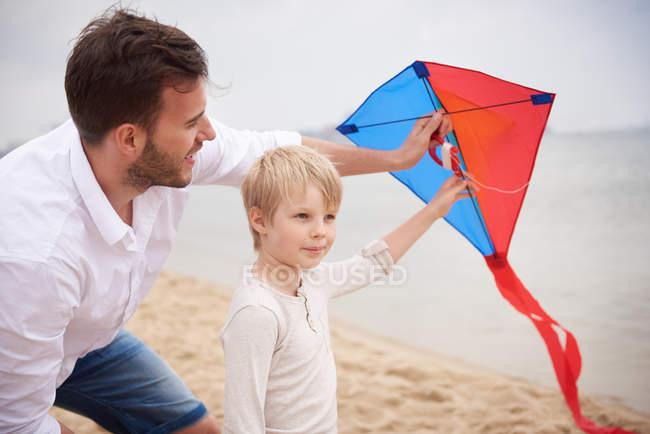 Père et fils jouant au cerf-volant sur la plage — Photo de stock