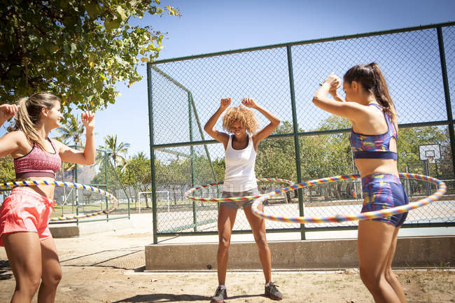 Three young women with hula hoops around waist, outdoors — Stock Photo
