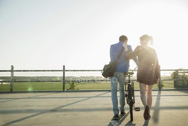 Jeune couple poussant vélo dans un parking vide — Photo de stock