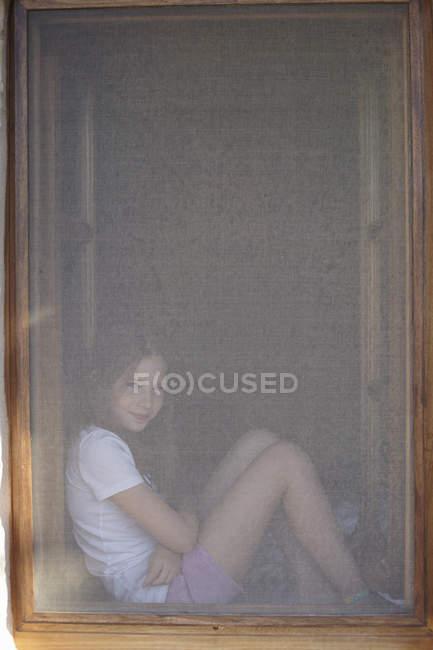 Retrato de niña sentada en un marco de ventana oscurecido - foto de stock