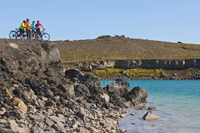 Quatre cyclistes avec des vélos hybrides regardant au-dessus du lac de cratère, Graenavatn, Krysuvik, Reykjanes, Islande — Photo de stock