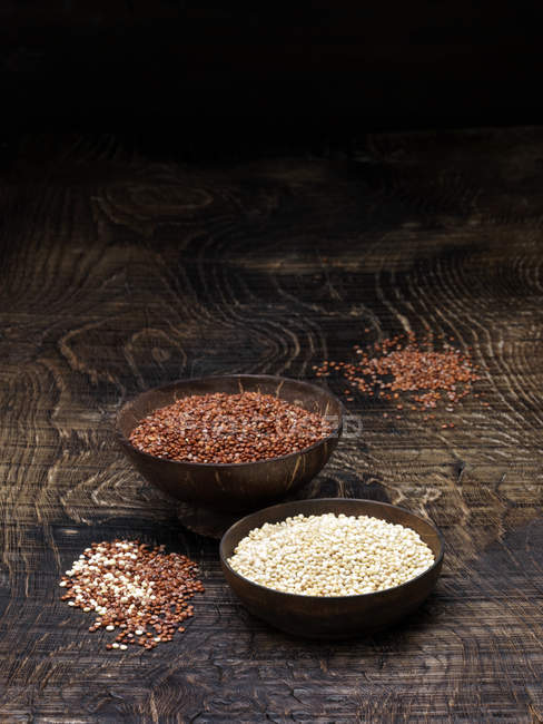 Nature morte avec bols de quinoa rouge et graines de quinoa blanc — Photo de stock