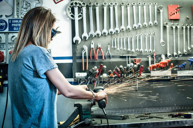 Female mechanic grinding metal in workshop — Stock Photo