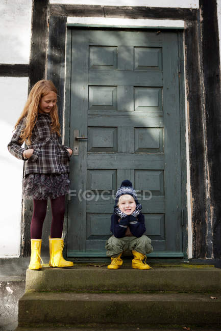 Brother and sister smiling on doorstep — Stock Photo