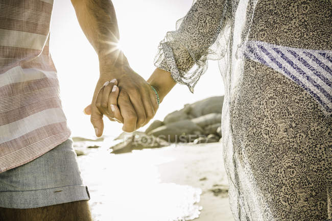 Couple holding hands while walking on beach — Stock Photo