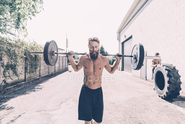 Young male cross trainer weightlifting barbell outside gym — Stock Photo