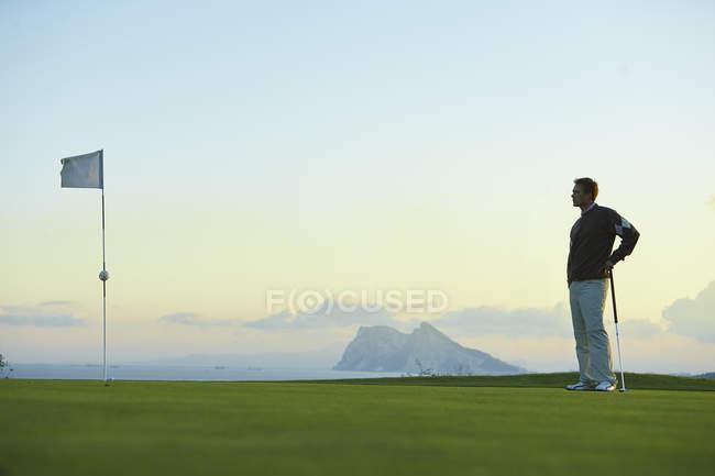 Golfspieler hält Golfschläger in der Nähe der Golffahne und schaut weg — Stockfoto