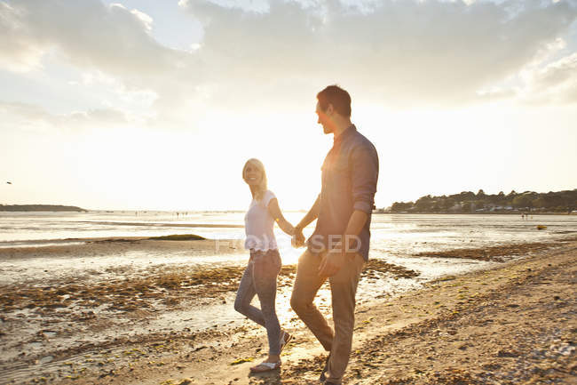 Young couple walking on sunny beach — Stock Photo