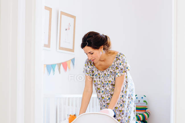 Pregnant mid adult woman arranging soft toys in child nursery — Stock Photo