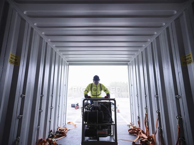 Сотрудник аварийно-спасательной группы разгрузки оборудования из грузового контейнера — стоковое фото